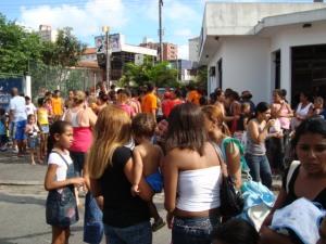 Multidão no ponto de distribuição de refrigerantes.