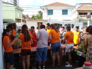 Voluntários servem refrigerantes e lanches às famílias carentes.