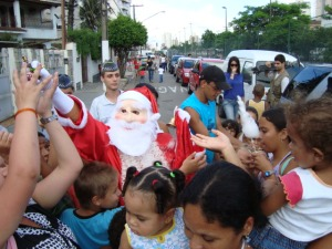 Crianças carentes e adultos,recepcionam o Papai Noel.